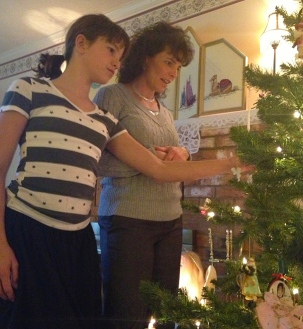 Ryleigh and Michelle admiring ornaments that record our family history.